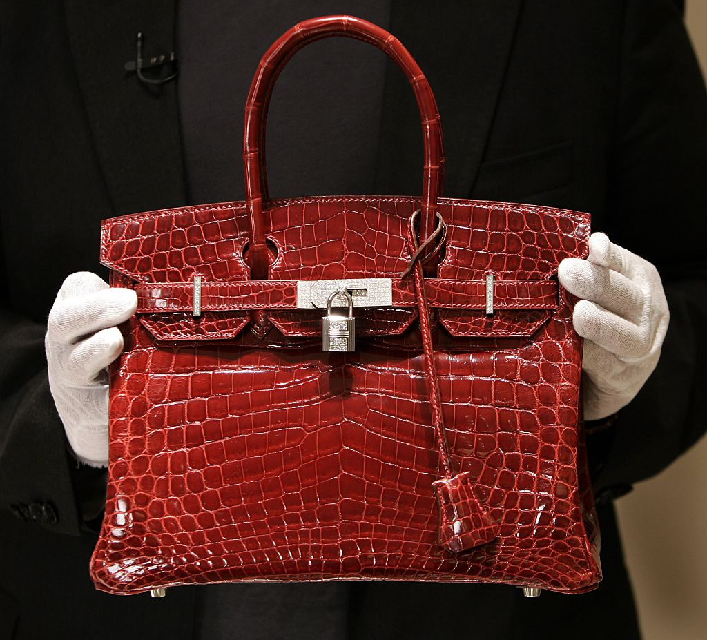 A employee holds a 129,000 USD crocodile Hermes Birkin Bag for the press to see during a private opening for the new Hermes store on Wall Street in New York bag available through the luxury concierge services of alfaone